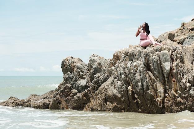 Fit vrouwelijke jogger die op rotsen op het strand rust en vers water drinkt na de training