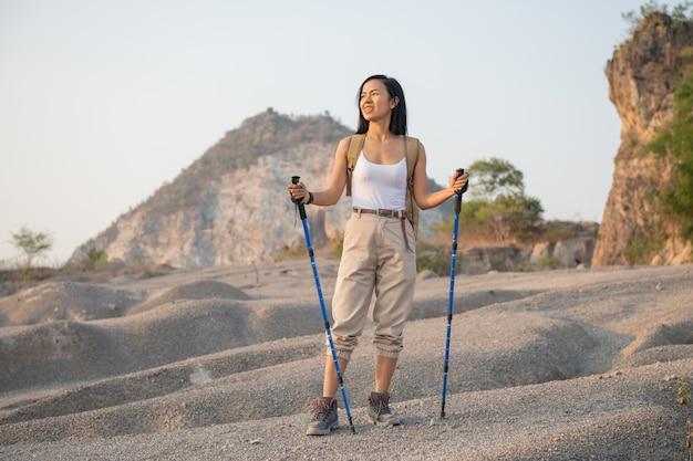 Fit vrouwelijke wandelaar met rugzak en stokken staande op rotsachtige bergkam uitkijkend op valleien en toppen.