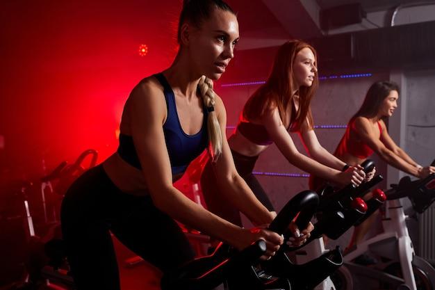 Fit vrouwen in de sportschool rijden op een draaiende fiets in rode neon verlichte rokerige ruimte. gezonde levensstijl en sportconcepten