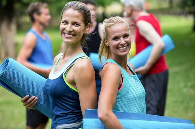 Fit vrouwen poseren met sportmatten rug aan rug
