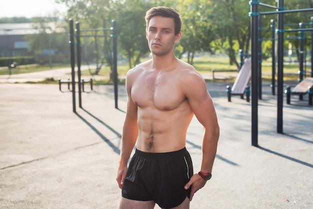 Fitnesmens het stellen op de post van de straatgeschiktheid die zijn spierlichaam tonen