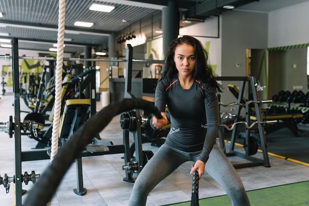 Fitness aan de touwen. mooie vrouw in sportschool trainen met touw. jonge vrouw hard trainen.
