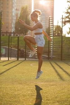 Fitness actieve vrouw met perfect lichaam springen in het park tijdens training