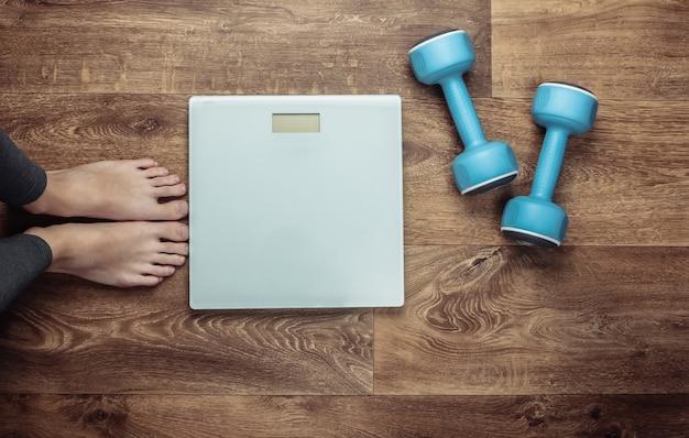 Fitness, afslanken concept. op blote voeten vrouwelijke benen, weegschalen, halters op de vloer.