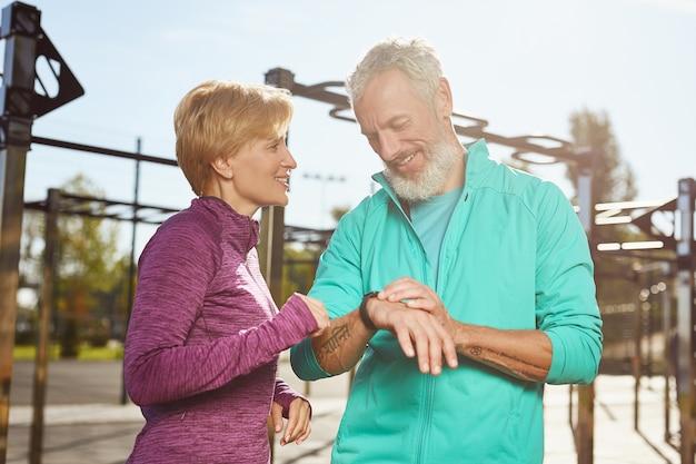 Fitness-app gelukkig volwassen familiepaar in sportkleding die trainingsresultaten controleert terwijl
