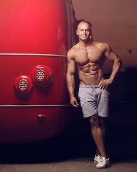 Fitness atletische man op straat in de buurt van rode bus. bodybuilding en gezondheidsconcept
