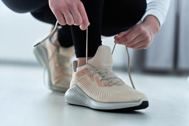 Fitness atletische vrouw bindt schoenveters op beige comfortabele sneakers en maakt zich klaar voor joggen en training. sport en wees fit. sportmensen met een gezonde sportieve levensstijl