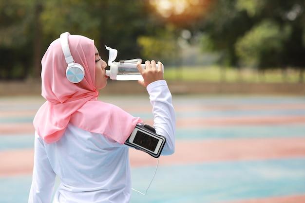 Fitness aziatische moslimvrouw die staat en water drinkt na het sporten.