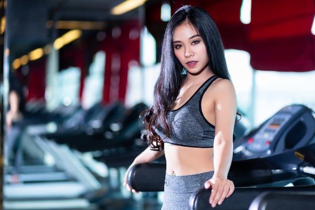 Fitness aziatische vrouwen die doen oefeningen die de run op de loopband in het interieur van de sportgymnastiek en de gezondheidsclub trainen.
