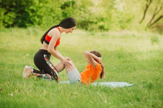 Fitness coach helpt meisje bij het voltooien van de oefening. maak sport in de open lucht.