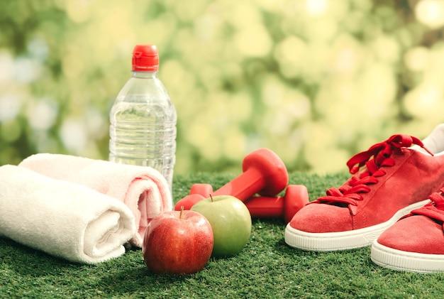 Fitness concept met fitnessapparatuur op groen gras achtergrond.