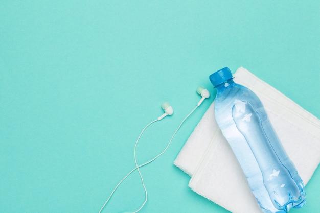 Fitness concept met fles water, mobiele telefoon met koptelefoon
