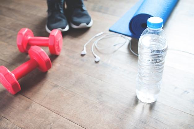 Fitness concept met fles water, sneakers, rode halters, yoga mat en koptelefoon op houten vloer, kopieer ruimte