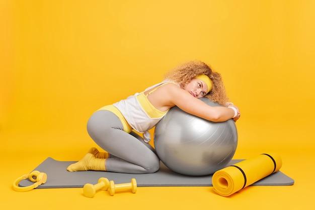 Fitness en aerobics concept. vermoeide, gekrulde vrouwelijke turnster leunt op fitball gekleed in activewear en gebruikt dumbbells voor het uitoefenen van poses op fitnessmat