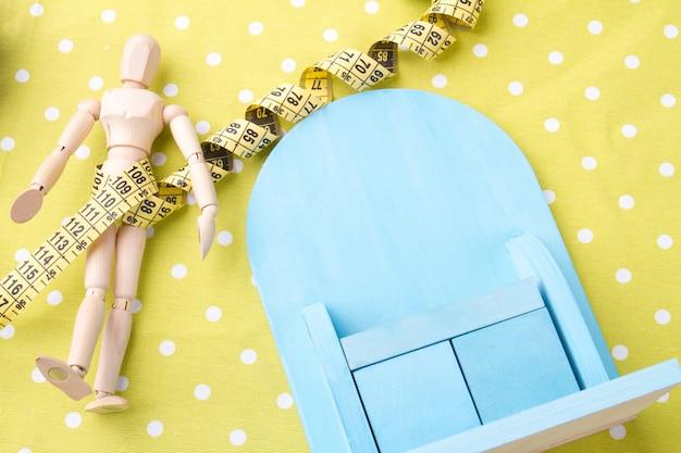 Fitness en gewichtsverlies concept miniatuur mannequin figuur met en miniatuur blauw op gele achtergrond