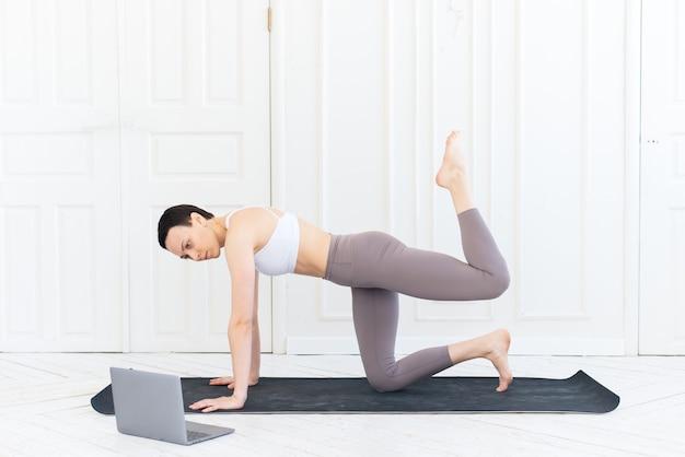 Fitness- en yogatrainer geeft les via laptop. online training. fit jonge vrouw die thuis traint, video-tutorial op laptop bekijkt.