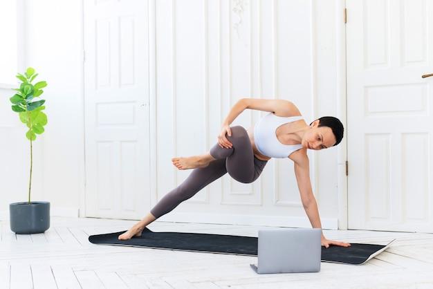 Fitness- en yogatrainer geeft les via laptop. online training. fit jonge vrouw thuis uitoefenen, video tutorial kijken op laptop.