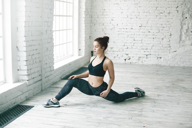 Fitness, fysieke oefeningen en een actief gezond levensstijlconcept. foto van aantrekkelijke jonge vrouw met perfect atletisch lichaam front splitst in grote zaal met kopie ruimte voor uw informatie
