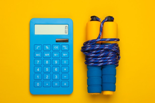 Fitness, gewichtsverlies stilleven. calorieën tellen. rekenmachine en springtouw op geel.