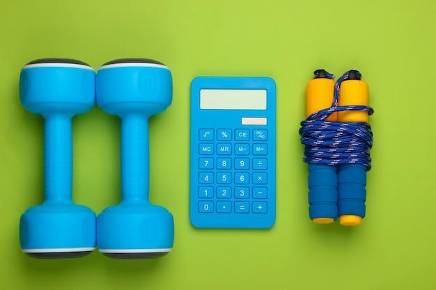 Fitness, gewichtsverlies stilleven. calorieën tellen. rekenmachine, halters en springtouw op groen. minimalisme. plat leggen