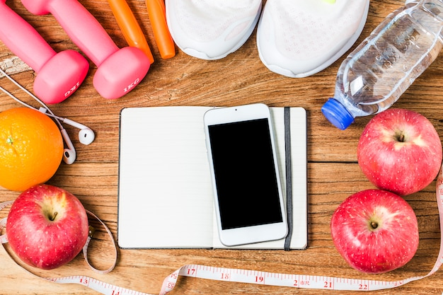 Fitness, gezonde en actieve levensstijl concept, fles water, domoren, sportschoenen, smartphone met koptelefoon en appels op houten achtergrond. kopieer ruimte voor tekst. bovenaanzicht