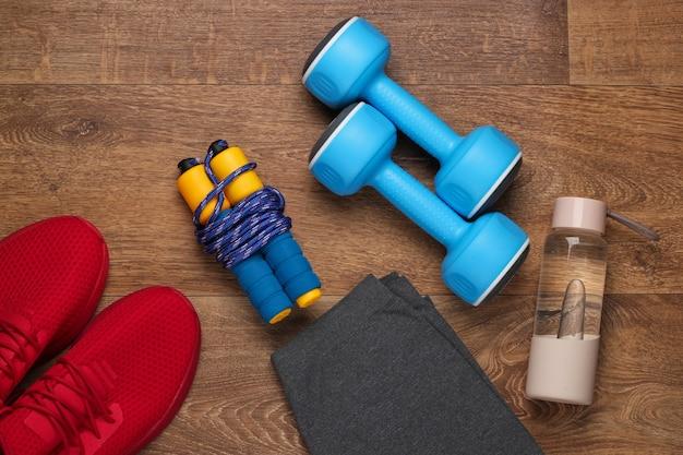 Fitness, gezonde levensstijl concept. rode sportschoenen, halters, fles water, springtouw op de vloer. bovenaanzicht