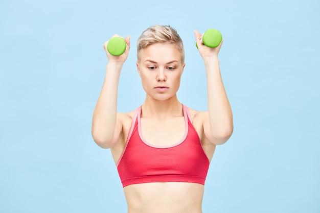 Fitness-, gezondheids- en sportconcept. geïsoleerde shot van atletische jonge europese blonde vrouw in stijlvolle rode top die biceps-krullen doet, twee groene halters optilt, armspieren opbouwt, gefocust kijkt