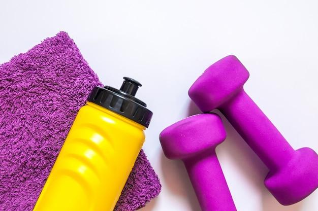 Fitness gym apparatuur. dumbbells met handdoek en wate bottler. workout schoenen. sport trainers op witte achtergrond. sport, gezonde levensstijl en objecten concept