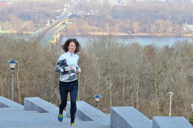 Fitness in de stad, vrouw runner joggen met prachtig uitzicht, hardlopen en buiten trainen in de winter