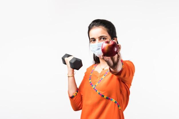 Fitness in pandemic-concept - vrij indiaas jong meisje draagt een medisch gezichtsmasker tijdens het sporten met dumbbell en het tonen van appel