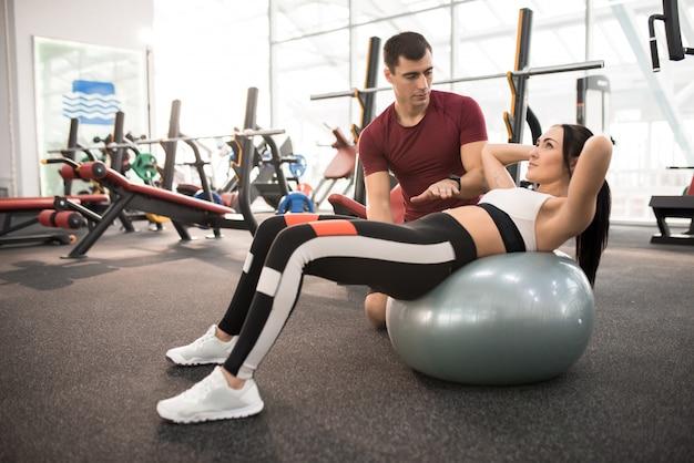 Fitness instructeur helpen jonge vrouw