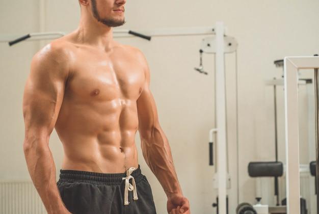 Fitness instructeur op de achtergrond van de sportruimte. mannelijk model met gespierde pasvorm en slank lichaam. sport concept