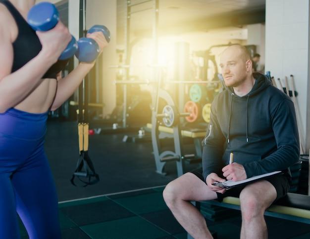 Fitness instructeur superviseert en notities in notitieblok resultaten van de opleiding van jonge atletische blonde uitvoeren van oefeningen met halters in haar handen op sportschool