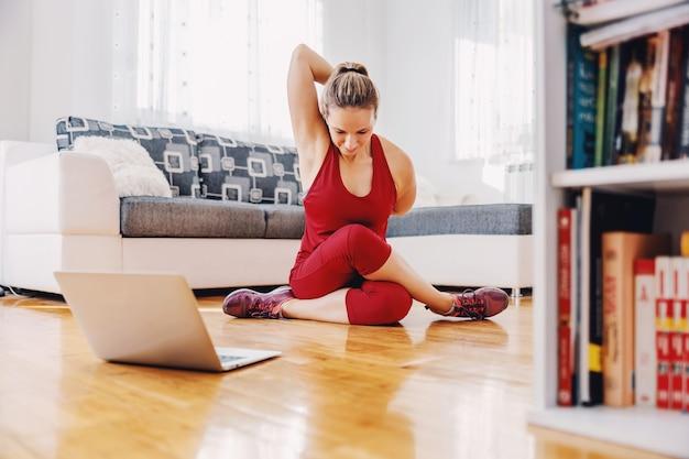 Fitness instructeur zittend op de vloer thuis en oefeningen uit te leggen aan de student