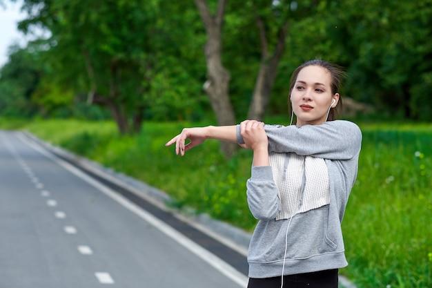 Fitness jonge aziatische vrouw handen uitrekken na het lopen.