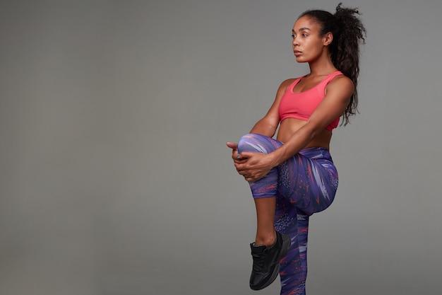 Fitness jonge donkere huid krullend model met paardenstaart kapsel poseren in sportieve roze top en gedrukte leggins, spieren van haar benen uitrekken
