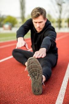 Fitness jonge man zittend op racebaan stretching oefening doen