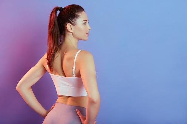 Fitness jonge mooie vrouw in grijze legging en witte tank top achteruit poseren met handen op de heupen, meisje met paardenstaart wegkijken, staande geïsoleerd op een achtergrond kleur.