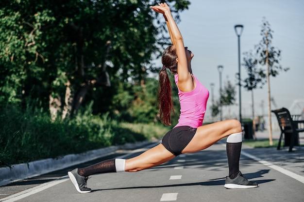 Fitness jonge vrouw benen strekken na run. buitenshuis sport portret