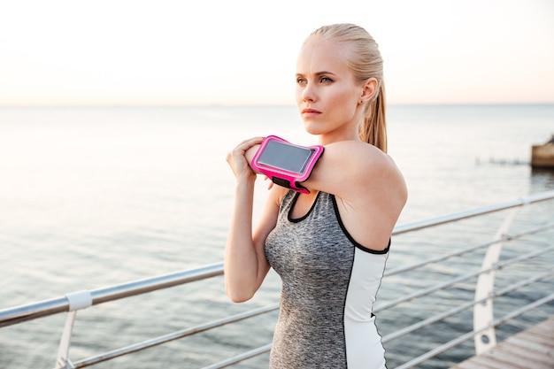 Fitness jonge vrouw doet rekoefeningen buiten op het strand pier