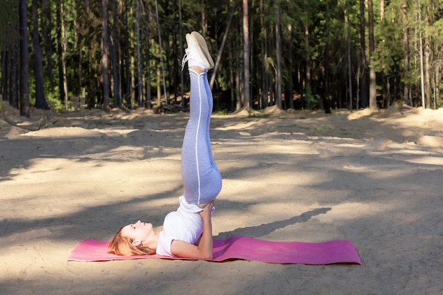 Fitness jonge vrouw met haar benen omhoog het beoefenen van yoga of pilates in het bos op het zand op de roze mat. uttana padasana (the raised-leg pose). zonnige zomerdag, zonsopgang in de ochtend.