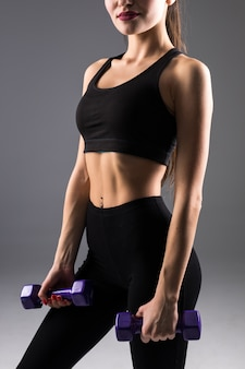 Fitness jonge vrouw met halters op een grijze muur. sport levensstijl.