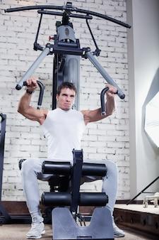 Fitness - krachtige gespierde man doet gewichtheffen in de sportschool