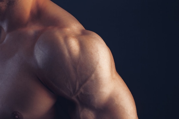 Fitness man achtergrond schouder biceps borstspieren triceps bodybuilder op een donkere achtergrond