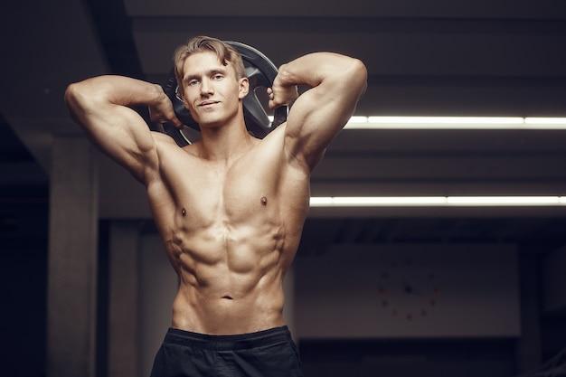 Fitness man bij training in de sportschool met bodybar spieren uitrekken