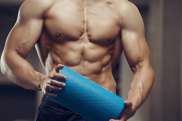 Fitness man bij training in de sportschool met massage roller spieren uitrekken. training fitness en bodybuilding concept. kaukasische bodybuilder die oefeningen in gymnastiek doet
