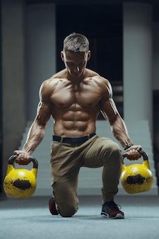 Fitness man bij training in de sportschool spieren oppompen met kettlebell.