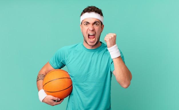 Fitness man die agressief schreeuwt met een boze uitdrukking of met gebalde vuisten om succes te vieren