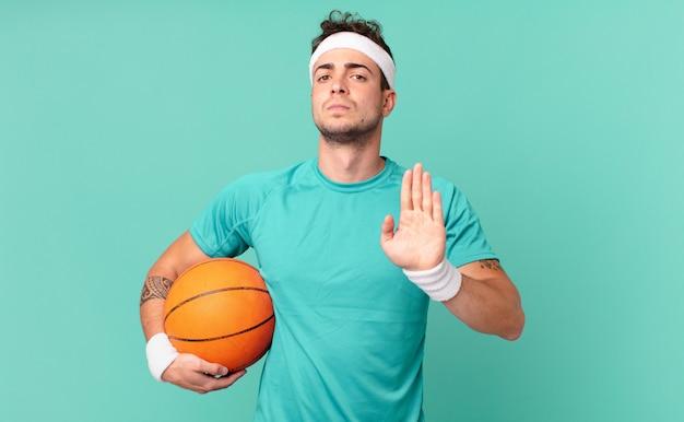 Fitness man die er serieus, streng, ontevreden en boos uitziet met een open palm die een stopgebaar maakt