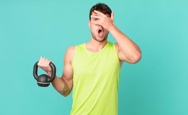 Fitness man die geschokt, bang of doodsbang kijkt, het gezicht bedekt met de hand en tussen de vingers gluurt